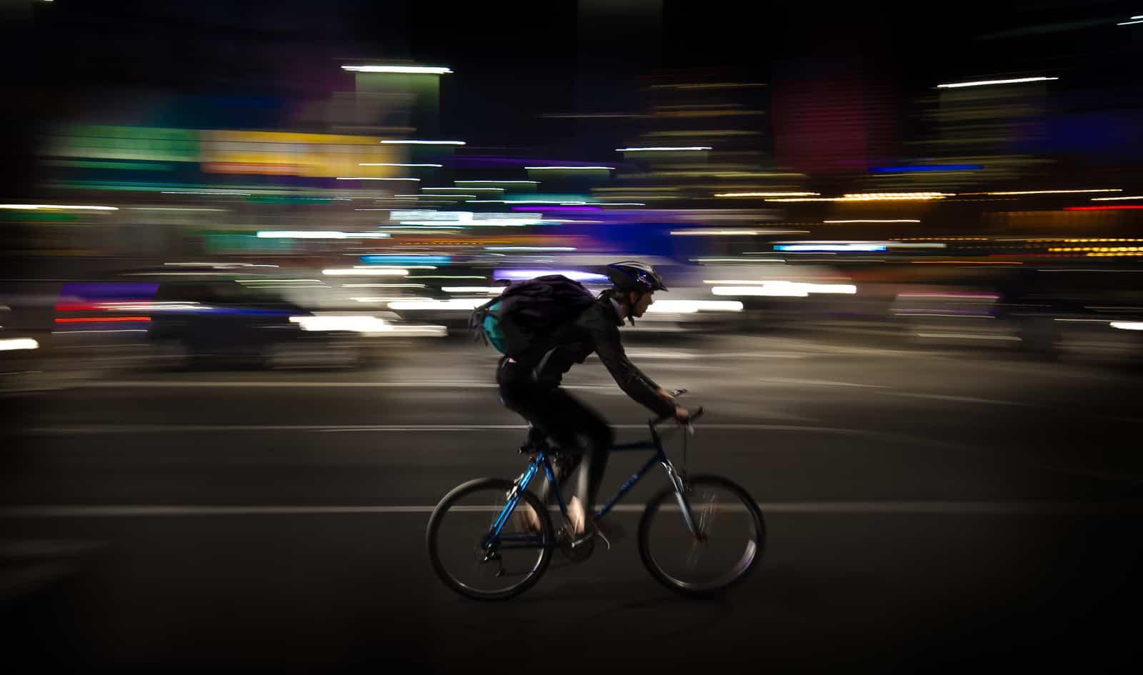 biker with mountain bike helmet lights at night