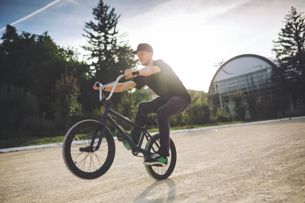 man doing tricks with lightweight bmx bikes